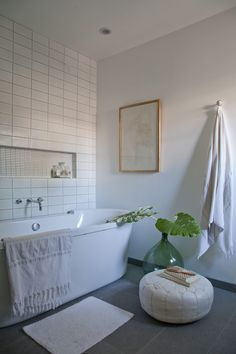 Stand alone tub with this white bathroom design feature tiled wall | Emily Henderson