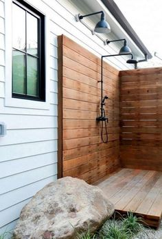 For this backyard retreat, deep bowl lighting brightens an outdoor shower!