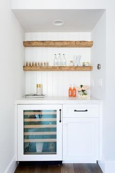 Rustic floating bar shelves are mounted against a white beadboard trim above a glass front mini wine fridge fixed beside white cabinets donning oil rubbed bronze pulls and beneath a white marble countertop. Floating Shelves Kitchen, Bar Shelves, Wood Shelves, Kitchen Storage, Glass Shelves, Rustic Shelves, Wine Storage, Open Shelving, Corner Shelving
