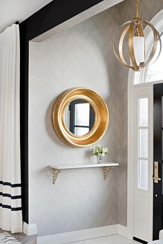 Stunning gray and gold contemporary foyer is fitted with a gold leaf convex mirror mounted to a wall covered in gray herringbone wallpaper above a brass and metal shelf illuminated by an antique brass sphere pendant. Grey Herringbone Wallpaper, Home Decor Trends, Foyer Decorating, Foyer Wallpaper, Marble Foyer, Herringbone Wallpaper, Contemporary Home Decor, Wallpapered Entryway, Interior Decorating Styles