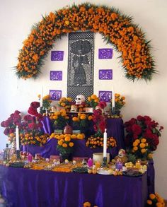 This altar looks very polished. The dark purple tablecloth contrasts nicely with the orange cempasuchitl flowers.