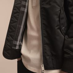 A Burberry bomber jacket with a lustrous technical outer. The soft, laid-back shape is finished with knitted trims and the zip pocket at the sleeve is inspired by the detailing on classic flying jackets.