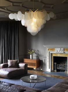 The low profile furniture allows for the largeness of the chandelier to not make the room feel cramped, though the color scheme is rather enclosed and cavelike.