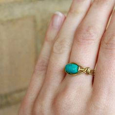 Gold Turquoise Ring; This ring features an oval reconstituted turquoise bead.