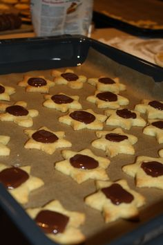 Schokoladen-Sterne - 100g kalte Butterflöckchen, 35g Zucker, 40g gemahlene Mandeln, 1 Tütchen Vanillezucker, Prise Salz und 125g Mehl verkneten. 1h abgedeckt kalt stellen.   Teig 1 cm dick ausrollen, kleine Sterne daraus ausstechen und jeweils ein Loch in die Mitte drücken. Im auf 160° vorgeheizten Backofen 10 min goldgelb backen.   50g Zartbitterschokolade grob hacken und in den Mulden der noch heißen Kekse schmelzen lassen. Bei Bedarf für weitere 1-2 Minuten in den noch warmen Ofen…