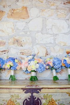Kristen and her bridesmaids carried soft-hued bouquets composed of David Austen roses, delphiniums, hydrangeas, peonies, and tuberose wrapped in cream ribbons. Photography: Meg Perotti. Read More: http://www.insideweddings.com/weddings/colorful-outdoor-wedding-at-northern-california-ranch-winery/444/