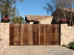 Tuscan Style Driveway Gate in Rustic Reclaimed Barn Wood With Decorative Dummy Hinges & Ring Pulls. Custom gate designs that are timeless! by DynamicGarageDoors