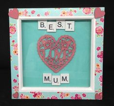 """White wooden scrabble letters saying """"Best Mum,"""" with a hand painted wooden heart saying love. Hand painted wooden hearts on the corners of the frame. Frames are white,Wooden with a floral trim. Scrabble Letters, Mothers Day Presents, Wooden Hearts, Gift Guide, Hand Painted, Personalized Items, Frame, Floral, Pictures"""