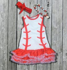 ***PRE-SALE*** Girl's baseball dress for infant girls, toddler girls, and girls to size 6/7.  This trendy little girl's dress is white with red baseball print and lots of super soft ruffles! (no itching) It's perfect for that little cheerleader, little sister, or any baseball, t-ball, or softball fan!     THIS DRESS IS IN HIGH DEMAND! Don't wait to reserve the size you need!    Add embroidery (monogram, name, sports #, etc) to make it all her own! A last name on the back of this dress and…