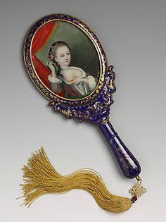 Hand-held mirror in blue enamel painted in gilt with floral motif and scrolls showing Western influence. On the reverse of the mirror, painted on glass is a portrait of a woman in Western dress but of Chinese appearance. Guangzhou, China. 1800-1825. Qing dynasty. Chinese export. Length: 11 in