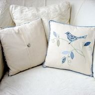 A beautiful appliqued cushion from our 'Little Bird' range, hand made in Stamford, Lincolnshire. It features a bird on a sprig of leaves in shades of blue in 100% natural fabrics on a background of cream american calico, widely used for quilts as it's ...