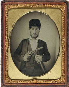 (c. 1861-1865) Confederate William C. Scott wearing fur cap with leather bill and holding Whitney revolver, 6th Texas Cavalry