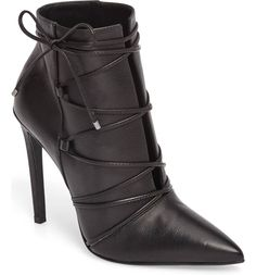 Slender straps tipped with gunmetal hardware secure a sharp boot featuring a wicked pointy toe and setback stiletto heel.