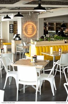 With its vibrant yellow booths and grey, concrete-like floors, Stacked Diner sports a contemporary and minimalistic aesthetic. | Photographer: Darren Bester