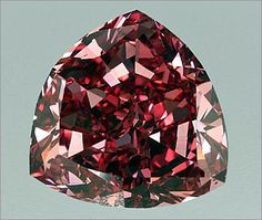 """The William Goldberg Diamond Corporation, famous for outstanding stones like the Premier Rose and the Guinea Star, cut this gem from a 13.90-carat rough. They transformed the piece into a spectacular red diamond weighing 5.11 carats. The GIA states, """"It is the largest Fancy Red, natural color diamond that we have graded as of the date the report was issued."""" The stone is a triangular brilliant, sometimes refered to as a trillion or a trilliant cut. It was cut sometime in the mid-1990s."""