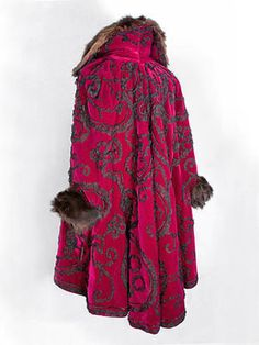 Appliqued coat c.1900  Magenta velvet coat trimmed with scrolling vines of ruched black chiffon, c.1900. Fur collar and cuffs.