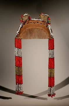 Philippines | T'Boli comb. Mindanao region.  Late 20th century | Little pieces of mirror are set into the wood and 2 prominences with brass wire and glass beads are decorating the top. On each side, series of tiny colored beads are hanging