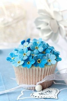 A perfect spring cupcake. Delicately decorated with blue flowers and kept simple with a white cake case.