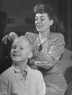 Actress Joan Crawford fixing her adopted daughter Christina Crawford's hair, with the 5-yr-old smiling proudly.