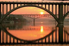 Tennessee River Bridges in Knoxville Tennessee, USA reflected in the waters of the Tennessee River.