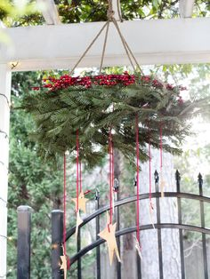 Wreath mobile: First, attach rope to three or four evenly spaced points along the wreath. Depending on how low the wreath is meant to hang, cut the rope to size, then attach to the ceiling or outside beam. Add decoration around the top of the wreath and suspend embellishments from the bottom for a layered effect.