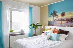 Makuuhuoneen Miami-teemaan haettiin lämpöä ja rentoutta. Sängyn yläpuolella oleva kuva ostettiin kuvapankista ja vedostettiin kapalevylle. Ikkunalaudalla olevat maskit ovat Meksikosta ja sängyn päädyn päällä olevat simpukat Arubalta. Tyynyt ovat Ellokselta ja H&M Homesta, päiväpeitto Ikeasta.