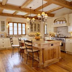 j'adore the french country look of this kitchen from the wood beamed ceiling, the wood-framed windows, the mantel over the stove, chandeliers, and the wooden island with antique turned legs = divine.