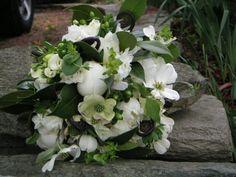 White peonies, white freesia, dogwood blossoms, green hypericum, bupleurum, camelia foliage, and fiddlehead fern curls.