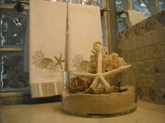 Love the shallow vase with sand and seashells for a bathroom!