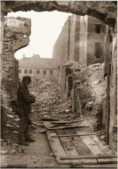 An SS soldier stands among ruins in the Warsaw ghetto during the suppression of the uprising.