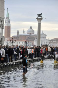 Tourists walk along raised gangways above the flood waters as others wade through the water in flooded St. Mark square as high tides reached 1.05 meters above sea level, partly flooding the city of Venice, Italy, Monday, Oct. 15, 2012. (AP Photo/Luigi Costantini)