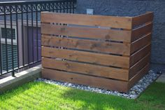 a custom built select grade eco stained cedar screen to hide an electrical unit.