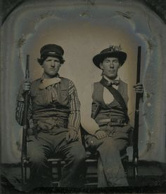 This rare tintype features two Missouri State Guard soldiers. On the right is Private P. S. Alexander of the Moniteau County Rangers; his comrade is Private S. W. Stone of the California Guards. Both are dressed in civilian clothing, typical of the Missouri State Guard. Stone is wearing an elaborate tooled leather sheath with a Bowie knife and is holding a musket, while Alexander is holding a civilian half-stock rifle and has a large knife in his belt. A bouquet of flowers adorns his hat.
