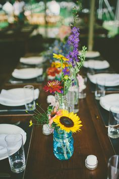 rustic floral centerpieces in mason jars http://www.weddingchicks.com/2013/09/25/colorful-backyard-wedding/