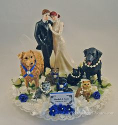 Customized wedding cake topper with dogs, cats and bride and groom.  Australian shepherd, black lab and 5 cats. Personalized red hair bride and medium brown hair groom.  Shown in ivory with royal accents. Includes name and wedding date plate. http://www.affectionately-yours.com/yours-mine-and-ours-wedding-cake-topper/