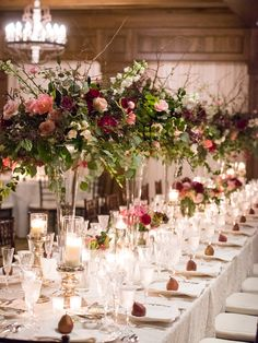 spectacular head table featured tall lush arrangements of black finesse rose, pink floyd rose, double pink tulip, light pink ranunculus, quicksand rose, white majolik spray rose, white delphinium, pink quince, burgundy snaps, bleeding heart vine, smoke bush, globe eucalyptus, seeded eucalyptus & hanging pepper berry on tall glass trumpet vases amid mercury glass candlesticks, bridesmaids bouquets and pears at each place setting.