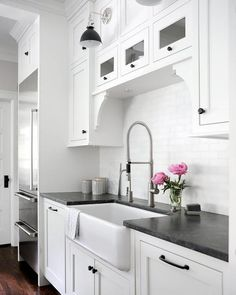 Lovely, bright and airy kitchen featuring white shaker cabinets with oil rubbed bronze hardware and black leather granite countertops finished with white subway tiles and a farm-style sink. Black Kitchen Countertops, White Shaker Kitchen Cabinets, White Granite Countertops, Butler Sink Kitchen, White Granite Kitchen, Ikea Kitchen, Kitchen Redo, White Cabinets, Cupboards
