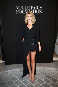 Rosie Huntington-Whiteley was stunning in a #VersusVersace FW15/16 look. She wore a black blouse and black asymmetrical skirt, one side comprised of a pleated mini-skirt with leather detailing. #VersaceCelebrities