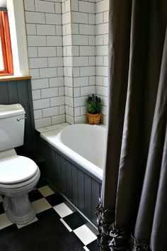 A stylish bathroom with monochrome floor tiles, subway wall tiles and dark grey painted tongue and groove in a pretty English country cottage.