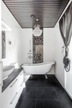 A black ceiling and floor, intricately pattered tile, and a chandelier give this bathroom an air of minimalist glamour. Black Ceiling, Clawfoot Bathtub, Natural Wood, Chandelier, Minimalist, Flooring, Bathroom, House, Design