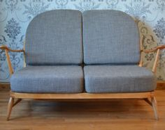 This is a beautiful blond 203/2 two seater sofa from Ercol. The blond wooden frame has been carefully refurbished and refinished to bring out the woods natural sheen. It features the stylish curved elm sides, spindles to the back and long, stylish arms. The sofa has been rewebbed using traditional techniques and the highest grade Pirelli rubber webbing. Professionally reupholstered with new foam cushions, the covers are handmade using soft green/moss fabric. All cushions have zip fa...