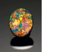 Very Fine Black Opal - Vivid hues of opals are created by tiny silica spheres that break white light apart. The size of the spheres determines the colors. 10.39 carats and measuring 16.5 x 13.0 x 6.5mm. This beauty is from Australia and sold for $68,000.
