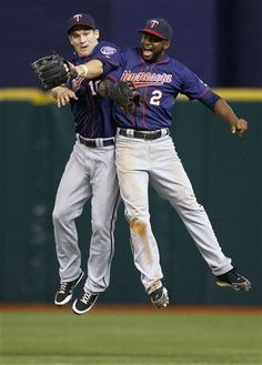 Minnesota Twins left fielder Josh Willingham (16) and center fielder Denard Span (2) celebrate after the team defeated the Tampa Bay Rays 5-4 during a baseball game Friday, April 20, 201