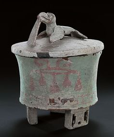 Teotihuacan, 350 - 550 A.D.  Height: 22,8 cm (with lid)  Diameter: 17,5 cm  ID IV Ca 46183  National Museums in Berlin, Ethnological Museum    Many stucco-covered vessels came to light in Teotihuacan. Often they are three-legged vessels with geometrically perforated legs. The production resembles the al fresco technique of the city's famous murals. Paint was applied to and rapidly soaked into the fine, still-wet layer of plaster.    The red motif on the light green of the outer wall has…