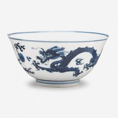 A Chinese blue and white porcelain bowl, jiajing mark, kangxi period, of rounded sides and everted rim, decorated in underglaze blue to exterior with two dragons chasing flaming pearls and to center of interior showing the moon overlooking the sea. D: 6 1/4 in.