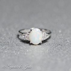 .925 Sterling Silver 8x7mm Oval Created Opal Cab 6 x 2mm Round White Cubic Zirconia Accent Stones 2.4mm Wide Band...