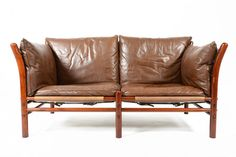 Gorgeous Swedish modern mid century safari- style two-seater leather sofa by Arne Norell. Constructed in jacaranda- stained beech and covered in