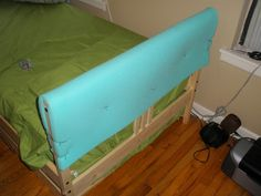 "1"" upholstery foam over the headboard, put a slipcover over it, and voila! A padded headboard."