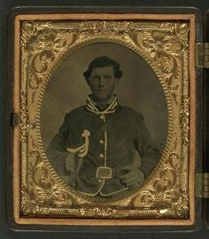 [Unidentified soldier in Confederate second lieutenant cavalry uniform with sheathed cavalry sword]: sixth-plate tintype, hand-colored ; 9.5 x 8.5 cm (case); Case: (front) Berg, no. 3-188; (back) Berg, no. 1-55. Photograph shows hand-colored gold piping indicating cavalry.