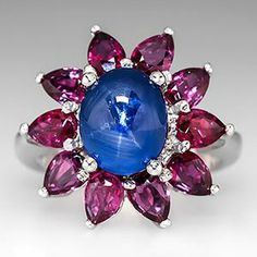 5 Carat Blue Star Sapphire & Ruby Cocktail Ring Platinum, This magnificent natural blue star sapphire and ruby cocktail ring features a large 5 carat cabochon sapphire in the center surrounded by 10 pear shaped rubies. The ring is crafted of solid platinum - EraGem